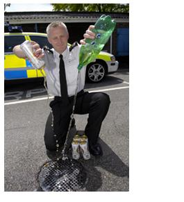 Policeman pouring drink down drain